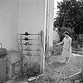 Mevrouw Wagner besproeit haar tuin met een tuinslang die verbonden is met een wa, Bestanddeelnr 255-4827.jpg