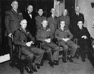 Formal portrait of a group of nine men. Four are sitting at the front and five are standing at the back. Six are wearing uniforms without headgear, while the other three are wearing civilian suits.