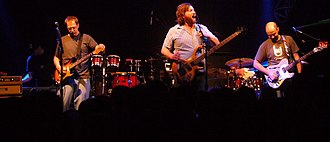 Moe (band) - moe. tuning their instruments between songs on March 3, 2007. Left to right: Jim Loughlin, Chuck Garvey, Rob Derhak, Vinnie Amico, Al Schnier.