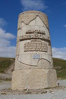 Цилиндрический каменный памятник с надписью внутри контуром Франции.