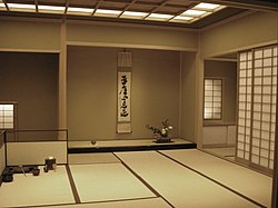 Interior view of a large tea room in summer, with tatami, and tokonoma with flower arrangement and scroll