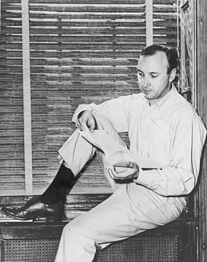 Mr. Neil Simon, author, sitting on windowsill ...