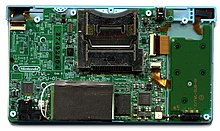 A large and small printed circuit board connected together. A metal chassis and main electronic components dominate opposite ends of the large PCB.