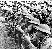 A large number of well equipped Asian soldiers sitting in rows on the ground, wearing pith helmets and holding assault rifles.