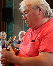 A white-haired man in a red T-shirt plays mandolin.