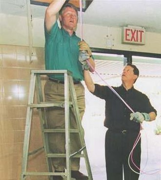 Al Gore - President Bill Clinton installing computer cables with Vice President Al Gore on NetDay at Ygnacio Valley High School in Concord, CA. March 9, 1996