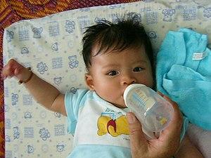 5 months old baby boy sucking milk (family mem...