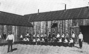 """Coeur d'Alene, Idaho labor confrontation of 1899 - Prisoners drill with wooden rifles in the """"bullpen,"""" Wardner, Idaho, 1899."""