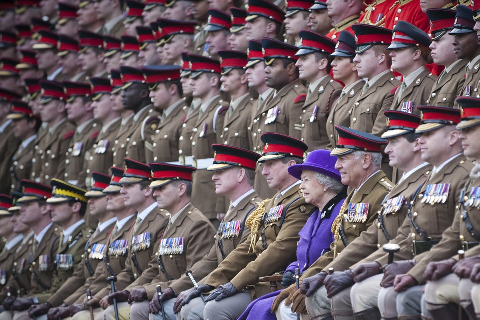 Queen Elizabeth II posing for a photograph with soldiers from the Household Cavalry, at Combermere Barracks in 2012.
