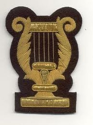 Royal Artillery Band - The RA Band lyre, (No. 1 dress version) as worn only by the Royal Artillery's musicians, and on the right forearm (rather than the standard army 'bandsman's lyre' which is worn by all other Army bandsmen and musicians, on the upper arm)