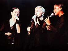 Image of a three females. They are wearing black and holding michophones.