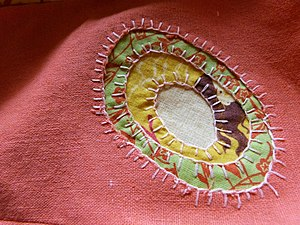 Appliqué - A reverse appliqué decorating a linen dress.