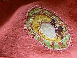 Appliqué - A reverse appliqué decorating a linen dress.