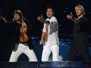 Dima Bilan - Dima Bilan performing at the Eurovision Song Contest final in Belgrade, 2008. He is accompanied by Edvin Marton (left) and Evgeni Plushenko (right).