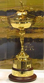 A gold cup set against a background of a lake and fields