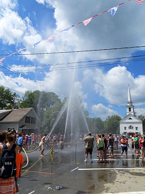 Saxtons River, Vermont - Start of a game of water polo on Main St, Saxtons River, after the 4th of July parade in 2013. The game is played by volunteer firefighters with fire hoses, trying to spray the ball down the street to a goal. Looking west at the Saxtons River Historical Society (a former Congregational church).