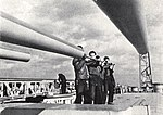 Sailors clean the 155 mm gun barrels aboard USS Denver (CL-58), circa in 1943.jpg