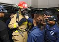 Sailors practice wearing fire fighting gear. (8407483909).jpg