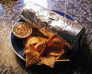 Plate with foil-wrapped burrito, chips and salsa