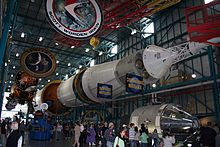 The Saturn V rocket is displayed horizontally, its engines at the left and the command module at its top on the right. Above it hangs large circular logos of each of the Apollo missions.
