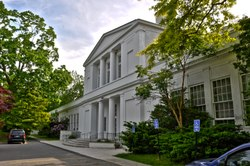 A two-story white Neoclassical school building