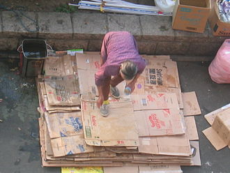Waste picker - A scavenger in Hong Kong pours water onto the paper she has collected in order to increase her profit by adding to its weight.