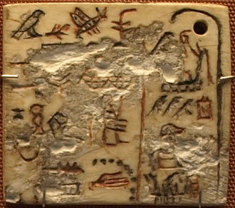 Semerkhet - Ivory label of Semerkhet, on display in the British Museum. The right section, introduced by the 'year'-sign Renpet (a bald palm stem), reports -from top to bottom- a feast of the Sokar-bark, a visitation to the temple of the ancestor-deity, Wer-Wadyt, and the travelling in a royal boat. The left part of the label shows the throne name Iry-Nebty of Semerkhet with a blessing wish below. On the upper left corner is described the content of the jar, to which the label was once adjusted. Also the name of the high official Henuka is preserved, who was obviously responsible for the delivery of the mentioned jar.