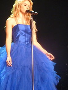 A woman with long blonde hair is singing in front of mic stand while dressed in a feathery blue gown.