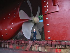 Propeller - Propeller on a modern mid-sized merchant vessel. The propeller rotates clockwise to propel the ship forward when viewed from astern (right of picture); the person in the picture has his hand on the blade's trailing edge.
