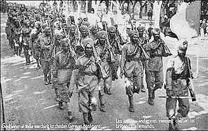 "Indian Army - French postcard depicting the arrival of 15th Sikh Regiment in France during World War I. The postcard reads, ""Gentlemen of India marching to chasten the German hooligans."""