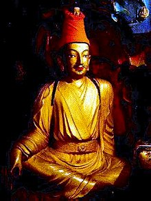 Gold-colored statue of Songtsen Gampo wearing a red cloth hat