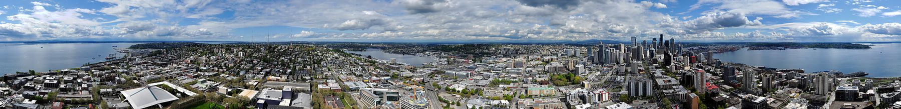 Panorama of Seattle as seen from the Space Needle: a nearly 360-degree view that includes (from left) Puget Sound, Magnolia, Queen Anne Hill, Lake Union, Capitol Hill, downtown Seattle, Elliott Bay, and West Seattle.
