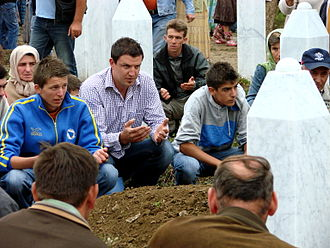 Persecution of Muslims - Mourners at the reburial ceremony for an exhumed victim of the Srebrenica massacre in Bosnia.