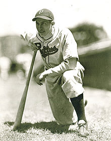 A baseball player is kneeling with one knee while leaning onto a baseball bat.
