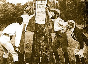 The Story of the Kelly Gang - The Kelly gang inspects a reward notice for their capture.