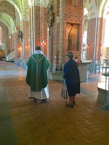 A Lutheran priest of the Church of Sweden prepares for the celebration of Mass in Strangnas Cathedral. Strangnas Cathedral interior.jpg