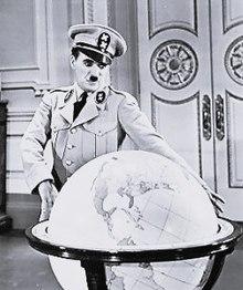 Capture d'écran montrant Chaplin en uniforme militaire avec une casquette à côté d'un large globe terrestre