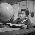 Topaz, Utah. A globe is used by this pupil in the high first grade, to assist in his geography lesson. - NARA - 536993.tif