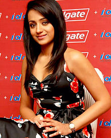 Trisha facing the camera while sitting against a red wall