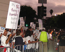 A crowd of people at the left are standing behind a gated barrier. The crowd is holding protest signs and the majority are looking away from the camera. An obscured man is being interviewed at the right side of the image. The sky appears to be approaching night.