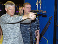 U.S. Air Force Col. William Mott, left, commander, 37th Training Wing, fires a 9 mm pistol simulator at the USS Missouri small arms marksmanship trainer at Recruit Training Command during a two-day visit by Air 100617-N-IK959-664.jpg