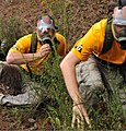 U.S. Airmen with the Joint Base McGuire-Dix-Lakehurst, N.J., comptroller team take cover after a chemical warfare scenario during a confidence course as part of Air Mobility Rodeo 2011 at Joint Base 110726-F-FC636-004.jpg