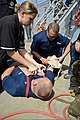 U.S. Navy Culinary Specialist 3rd Class Kiley Sosbe, left, and Ship's Serviceman Seaman Corey Gabbard simulated treating Gunner's Mate 2nd Class Corey Blakely during a medical training team drill 130517-N-ER662-050.jpg