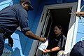 U.S. Navy Machinist's Mate 2nd Class Kevin Paulk, assigned to amphibious assault ship USS Nassau (LHA 4), delivers bleach to a resident during a food convoy to the neighborhoods affected by Hurricane Ike 080921-N-KD705-220.jpg