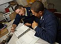 US Navy 041211-N-6495K-014 Machinist's Mate Chief Petty Officer Mark Johnson conducts an evaluation on a preventive maintenance spot check, with Machinist's Mate 3rd Class Edwin Vasquez.jpg