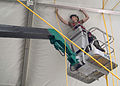 US Navy 070719-N-5253W-003 Construction Electrician Constructionman John Kinghorn, of Naval Mobile Construction Battalion Seven (NMCB 7), runs lines through the frame of a tension fabric structure at the Ikego Housing Compound.jpg