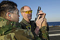 US Navy 081012-N-4954I-007 Gunner's Mate Seaman Joel Ramirez, left, from Glendale, Ariz. hands a 9mm pistol to Carrier Strike Group (CSG) 3 commander Rear Adm. Mark Vance, during a small-arms certification.jpg