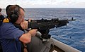 US Navy 090119-N-1688B-363 British Cmdr. Mark Fitzsimmons, director of staff for Africa Partnership Station (APS) 2009, fires the M-240 machine gun while aboard the amphibious transport dock ship USS Nashville (LPD 13).jpg