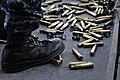 US Navy 120118-N-ZI635-361 Shell casings from a .50 caliber machine gun collect around the feet of Aviation Ordnanceman 3rd Class Jeffery Harris as.jpg
