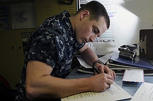US Navy 120215-N-RG587-033 Electronics Technician 3rd Class Marley Camden fills out a safety harness check out form in electrical tool issue.jpg